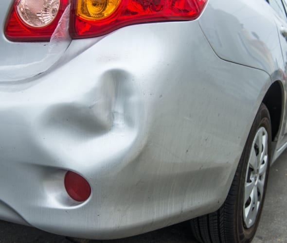 Photo of a car with a dented rear bumper