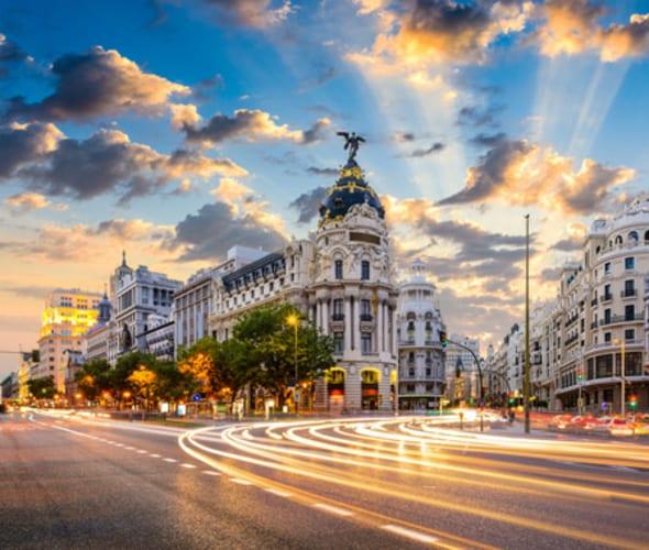 cars drive down an international city street