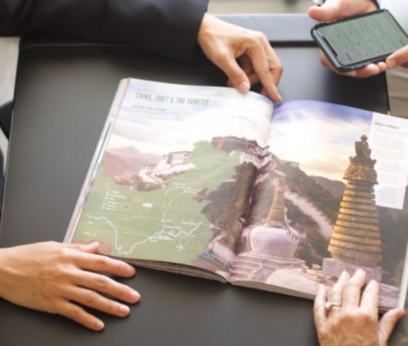 AAA Travel Agent shows a AAA vacation guide to China to a Member