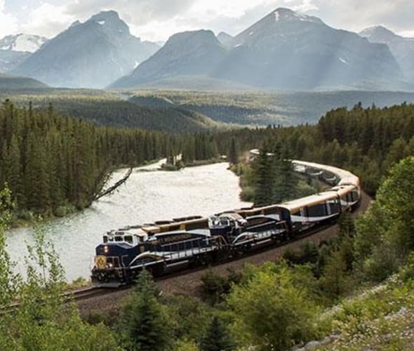 rocky mountaineer train next to a river