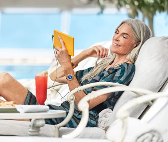 woman with device poolside on a princess cruise