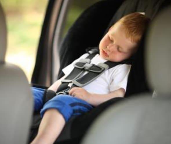 boy sleeps in booster car seat inspected by AAA technician