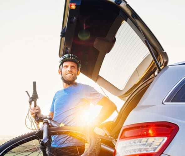 AAA Member unloading a mountain bike from his car at sunset