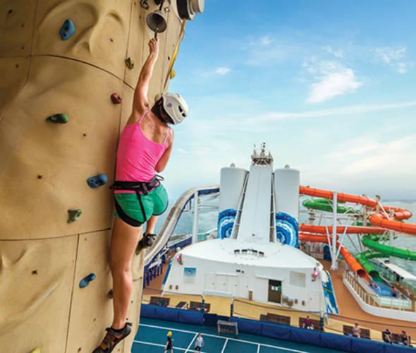 woman climbing rock wall on a royal caribbean cruise