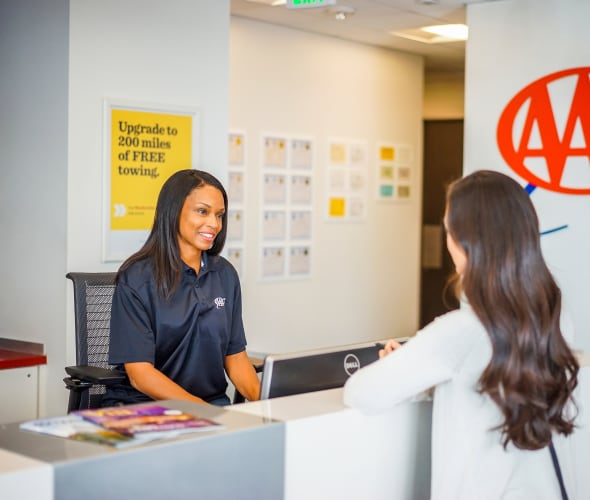 AAA member gets assistance from a AAA agent at a desk at a AAA office.