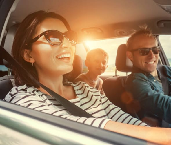 Family smiling in the car as they drive a Hertz rental car booked through AAA