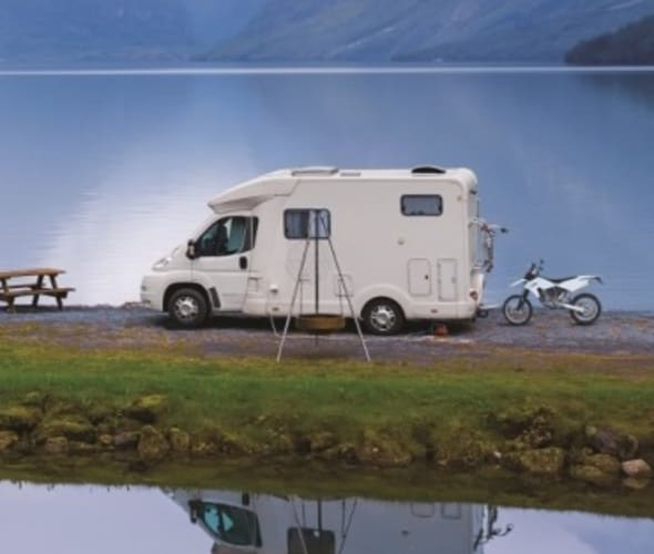 AAA Premier Members in their white RV by a lake