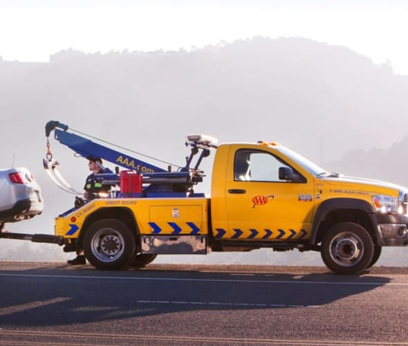 A AAA tow truck assists a car stranded on the side of the road.