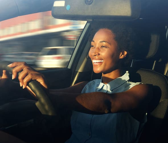 a smiling AAA member with AAA auto insurance drives her car