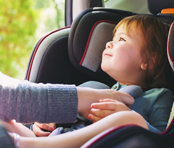 A mother brings her child to AAA for a car seat inspection