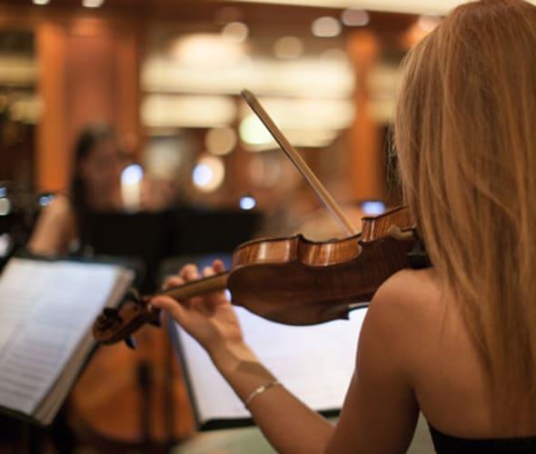 woman playing violin on cunard cruise