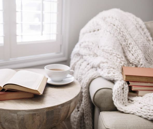 cozy armchair by window with throw, side table, books, cup of tea.