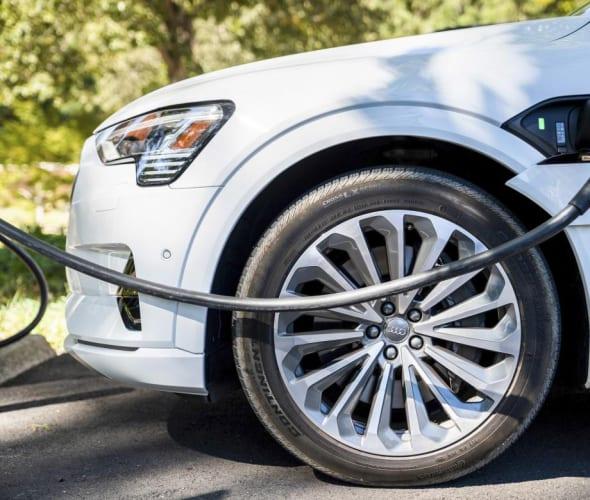 An Audi E-tron plugged into an EV charger.