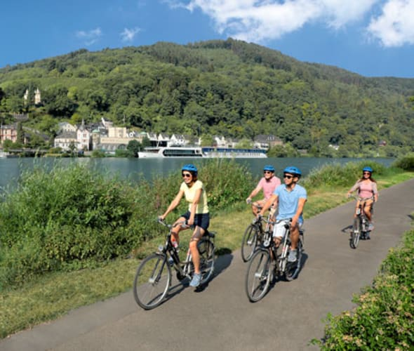people riding bikes next to a river with an amawaterways ship in the background