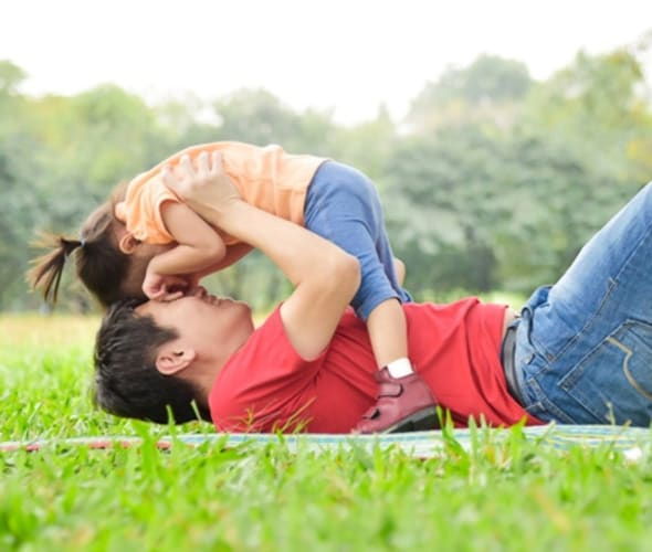 Father with AAA life insurance plays with his toddler daughter in a park