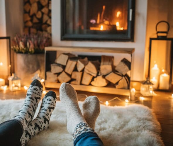 AAA Members sitting in front of a fireplace in winter