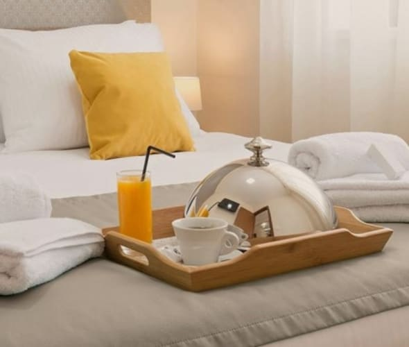 Hotel bed with breakfast tray