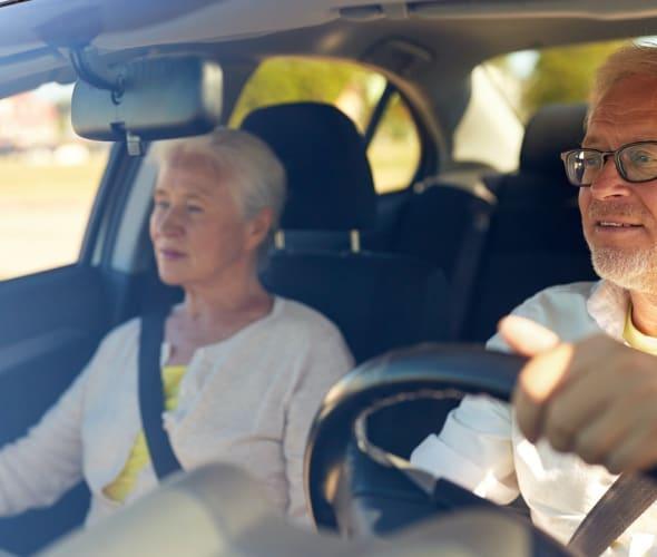 An elderly couple behind the wheel.
