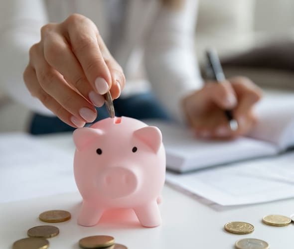 A woman with AAA Auto Insurance puts her savings in a piggy bank