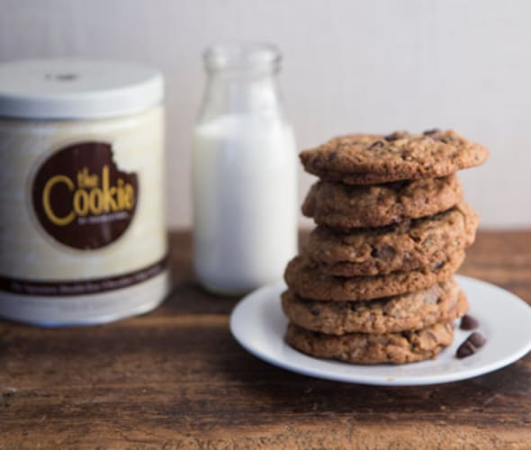 chocolate chip cookies on a plate with a glass of milk in the background