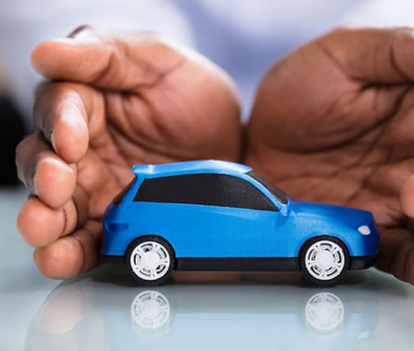 a pair of hands protect a blue toy car