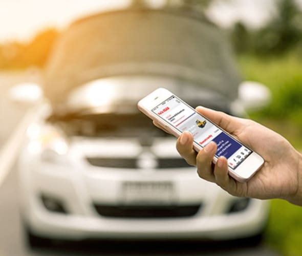 Hand of a AAA Member using the AAA app on their cellphone to call for roadside assistance, with broken down car in the background.