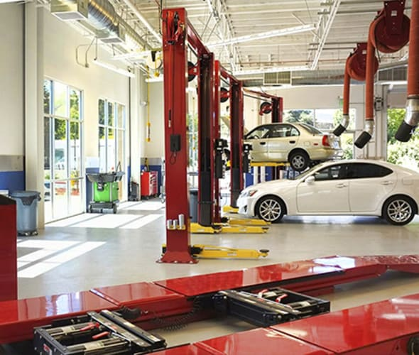 Inside of a AAA Auto Repair Center with car lifts and multiple cars.