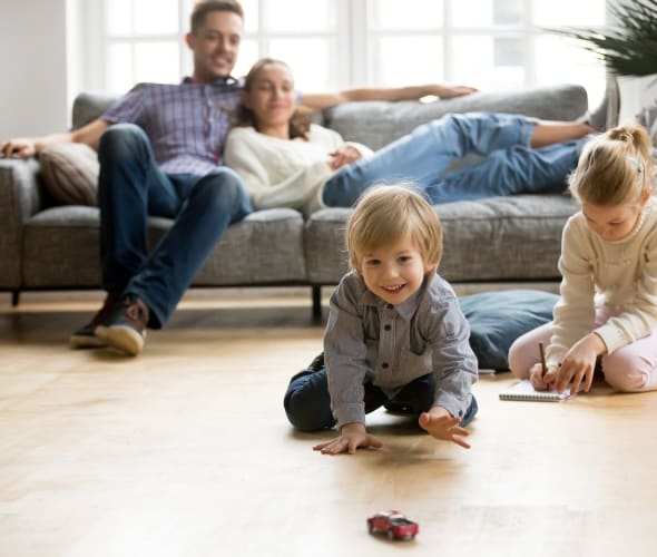 Little boy reaching for a toy car on the floor while his parents and sister watch