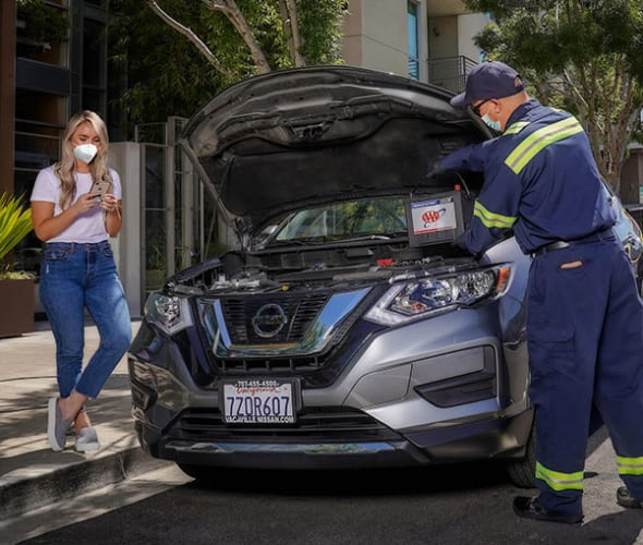 A Member of AAA has her battery replaced by a tow truck driver