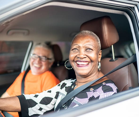 a retired AAA Member smiles from inside her car