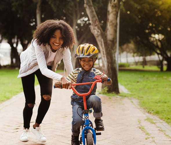 A AAA Life Insurance customer helps her son learn to ride his bike.