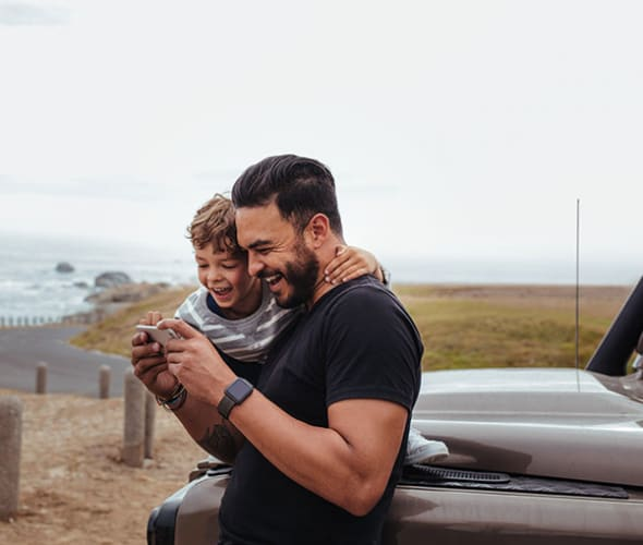 a AAA Member and his young son look at photos on a coastal road trip