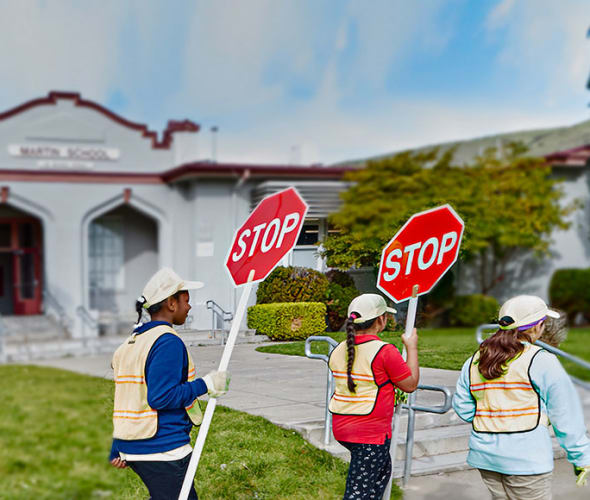 AAA School Safety Patrol students walking in a line in front of their school holding stop signs.