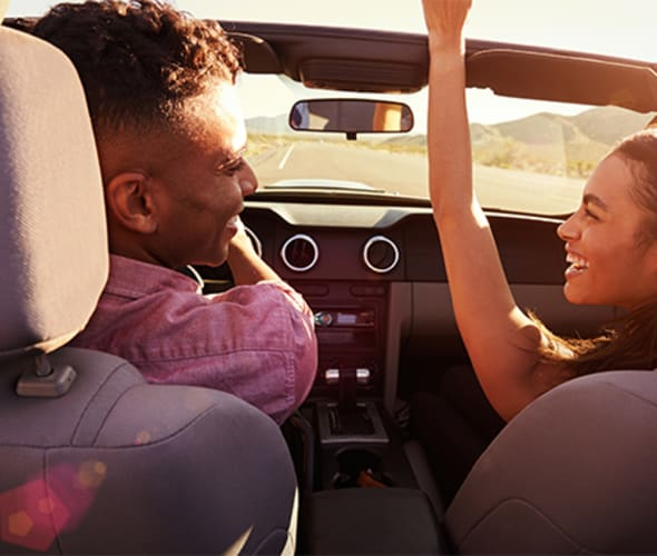 a couple taking a road trip in a convertible who saved money bundling AAA Home and Auto Insurance