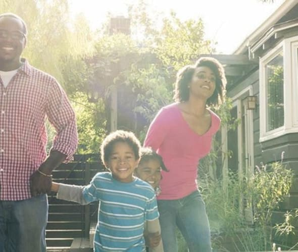 Family walks in the backyard of their home protected by AAA Insurance.