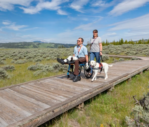 A couple and their service dog hike on a boardwalk trail in Yellowstone National Park.