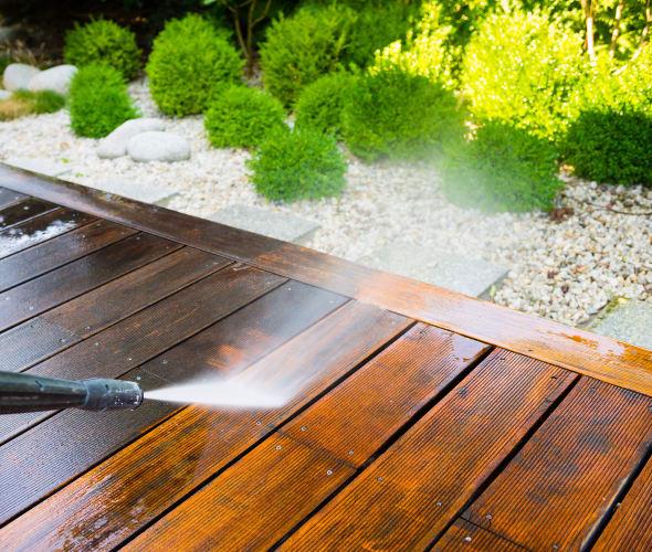 A homeowner pressure washes their deck.