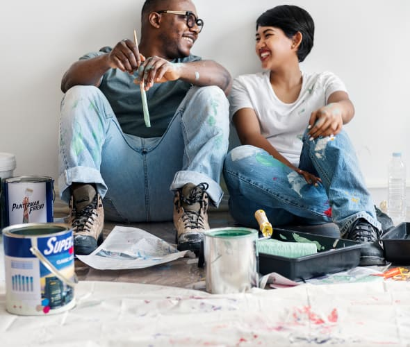 A man and woman sit against a wall before painting.
