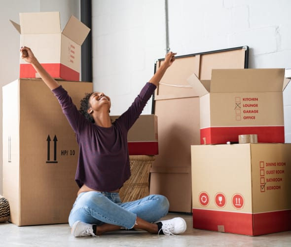 A woman sits in front of boxes in her new apartment.