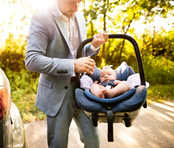 A father carries an infant in a car seat.