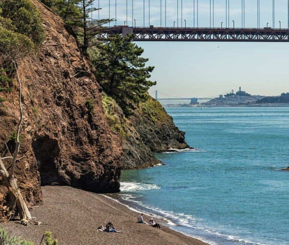 view from Kirby Cove towards the Golden Gate Bridge with San Francisco skyline on horizon.
