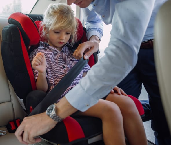 A dad buckles his daughter into her booster seat in the backseat of a sedan.