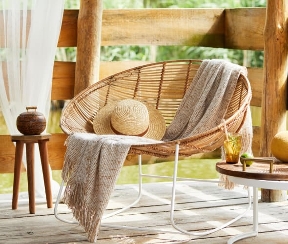 A rattan chair outside on a deck.