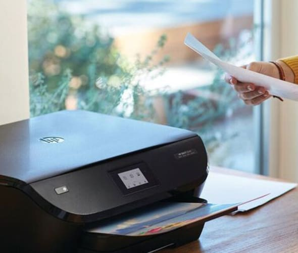 AAA member standing next to an HP printer on a desk