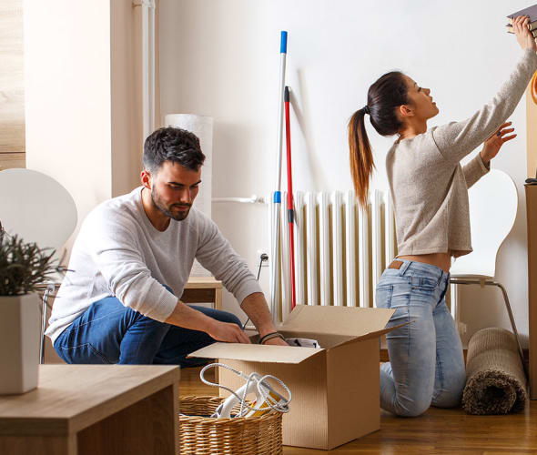 A man and woman unpack moving boxes in their new apartment with aaa renters insurance