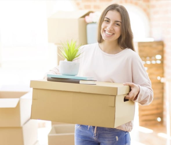 young woman smiles while she carries a box into her new apartment