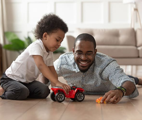 a AAA Member and his son play with a car on the floor