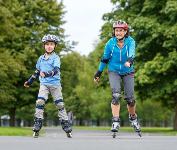 A AAA Term Life Insurance customer teaches her son how to rollerblade