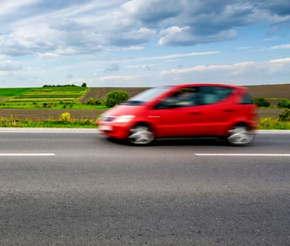 Small red car with AAA auto insurance coverage driving on a country road