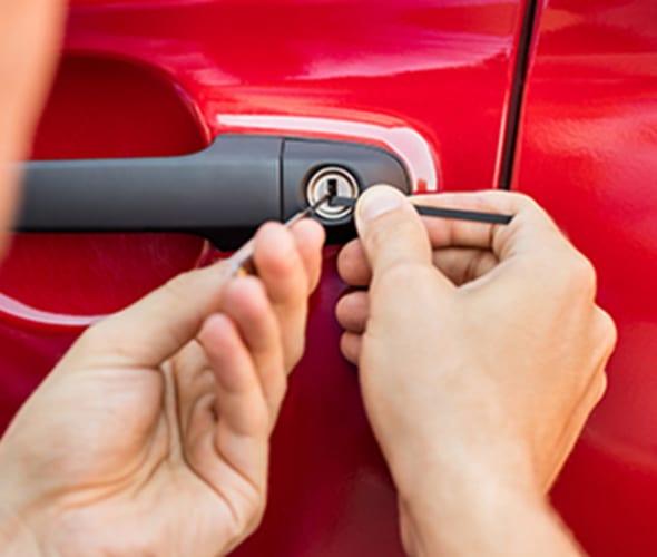 a aaa locksmith unlocks a red car door